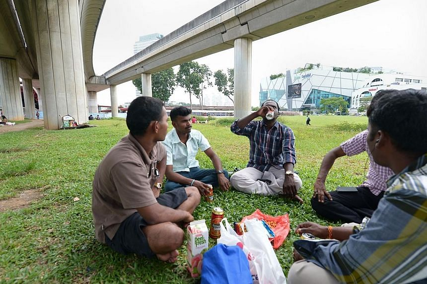 Workers hanging out at their regular meeting point under the railway tracks at Jurong East MRT.-- ST PHOTO:NG SOR LUAN