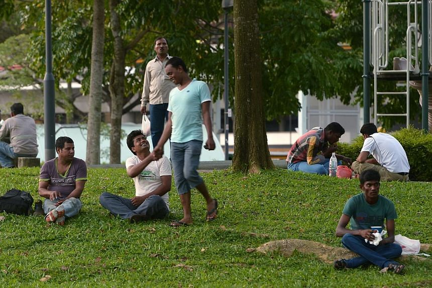 Foreign workers congregate at Jurong Central Park, next to Jurong Point , to meet up with friends and to relax. The park is however, quieter this evening, as some workers choose not to venture out of their dormitories.-- ST PHOTO:NG SOR L