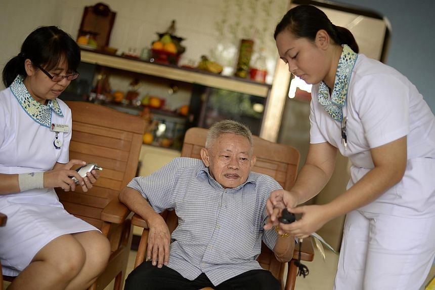 Senior staff nurse Serene Sng (left) and staff nurse Nursetiawati Abdul Rahman visiting Mr Lee Chee Keong, 73, at home to check on him. Mr Lee has breathing difficulties and often ends up in hospital. -- ST PHOTO: MUGILAN RAJASEGERAN