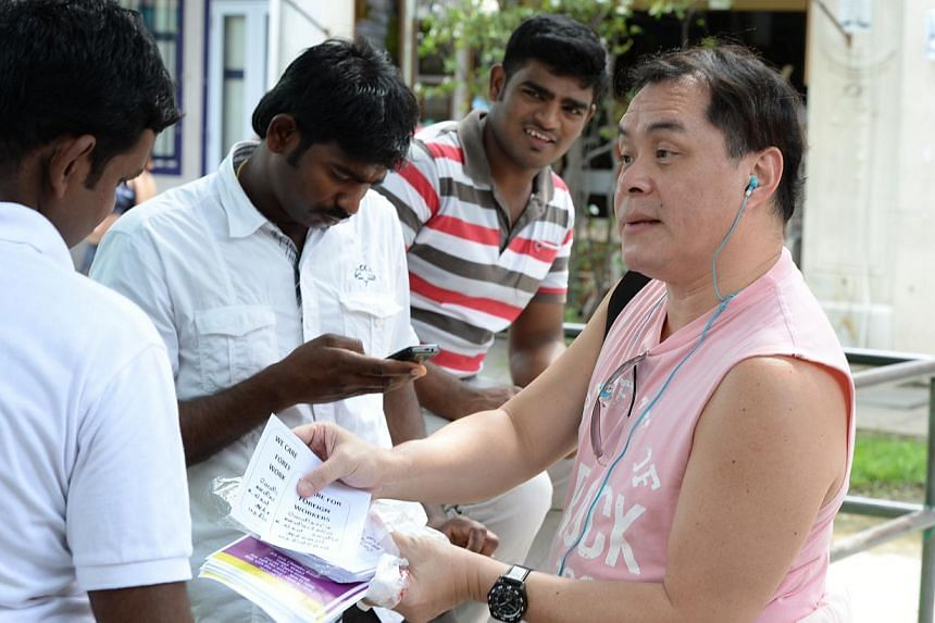 """Mr John Chan, 50, (right) handing out fliers to migrant workers around little India arcade. The flyer carries a message in English and Tamil saying """"We care for foreign workers"""".-- ST PHOTO: NADARAJAN RAJENDRAN"""