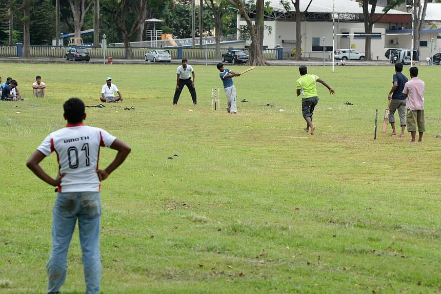 Migrant workers play cricket in a field at the junction of Hampshire road and Northumberland road, near race course road, on Sunday afternoon, Dec 15, 2013.-- ST PHOTO: NADARAJAN RAJENDRAN