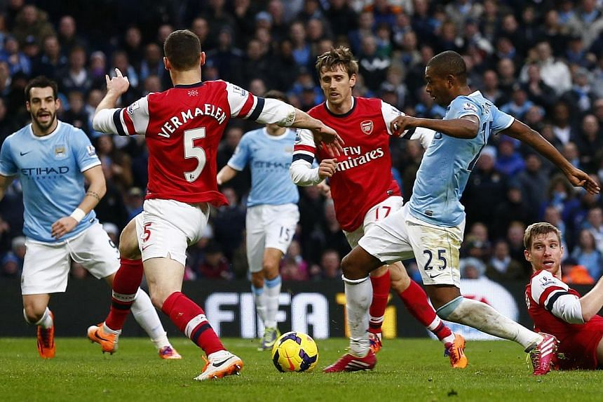 Manchester City's Fernandinho (second, right) kicks to score his second goal against Arsenal during their English Premier League soccer match at the Etihad stadium in Manchester, northern England, on Dec 14, 2013. -- PHOTO: REUTERS