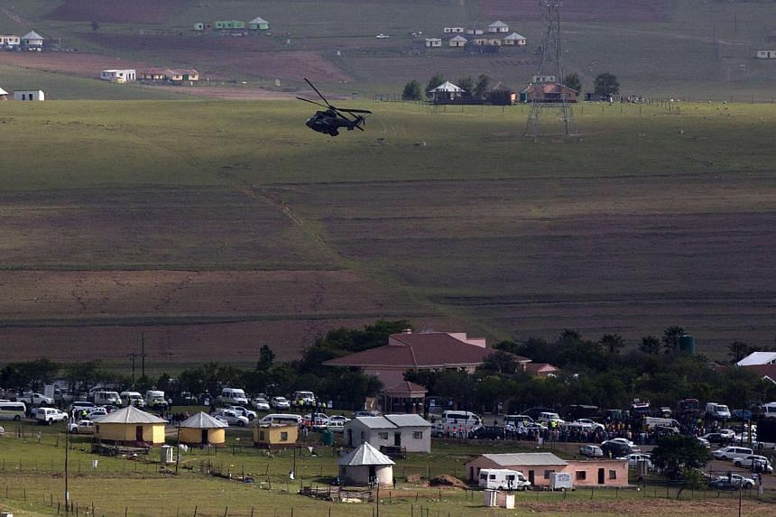 A military helicopter patrols the area as the hearse carrying the coffin of former South African President Nelson Mandela is escorted by a funeral procession after entering his home in Qunu, Eastern Cape on Dec 14, 2013. Nelson Mandela's remains were
