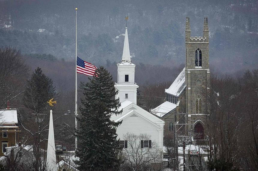 The town flag flies at half staff in Newtown, Connecticut on Dec 14, 2013. Church bells tolled 26 times in Newtown for the 20 schoolchildren and six adults massacred exactly a year earlier, as US President Barack Obama urged tougher gun controls. --