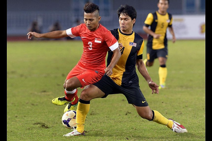 Sahil Suhaimi (left) and Mohamad Fadhli Mohd Shas challenge for the ball. Singapore versus Malaysia football match of the 27th SEA Games in Naypyitaw, Myanmar, Dec 15, 2013. Singapore drew 1-1 with Malaysia. -- ST PHOTO: LIM SIN THAI