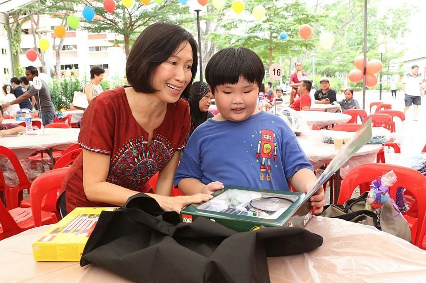 Grassroots adviser for Tampines Changkat and Member of Parliament for Tampines GRC Irene Ng (left) with Andrew See, 7, who studies at Pathlight School and received a Lego Star Wars torch and night light. Andrew is one of thebeneficiaries of the
