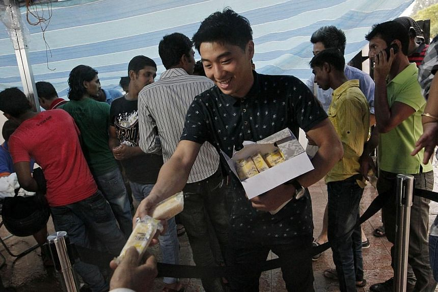Gaius Gay (centre), 23, a volunteer at Free Movement, gives out ice cream to foreign workers at a shop along Race Course Road, on 15 December, 2013.-- ST PHOTO:MARK CHEONG