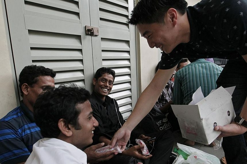 Gaius Gay (right), 23, a volunteer at Free Movement, gives out ice cream to (from left) Abdul Salam, 23, Mostafa Golam, 22 and Abdul Halim, 25, Bangladeshi workers who were having their meal along Race Course Road on Dec 15 2013.-- ST PHOTO:&nb