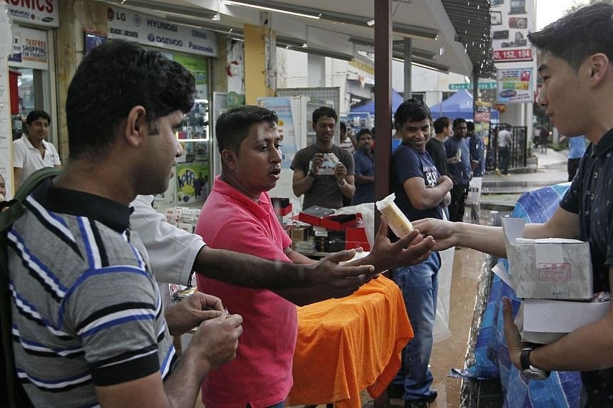 Gaius Gay (right), 23, a volunteer at Free Movement, gives out ice cream to Md Shamim (centre, in pink), 32, a Bangladeshi construction worker who was checking out shops along Little India on his off day, on Dec 15, 2013. -- ST PHOTO: MARK