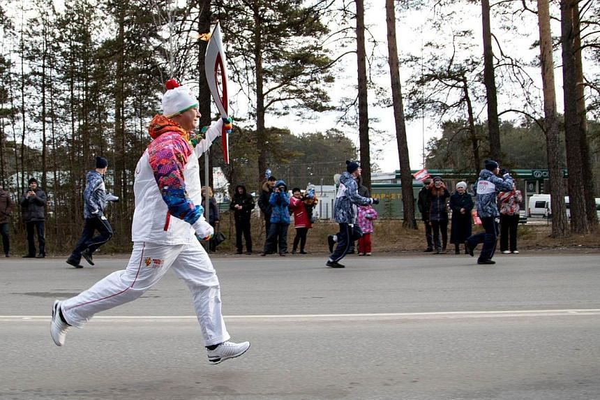 A torchbearer carrying an Olympic torch in Russia's Siberian city of Barnaul 3400 km south-east of Moscow, on Dec 3, 2013. -- FILE PHOTO: AFP/SOCHI 2014 ORGANIZING COMMITTEE