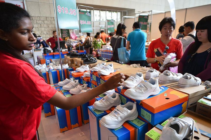 A salesgirl arranging shoes at the Back To School fair at the National Library. The two-day fair complements a voucher programme in which $125 tokens are given out to help children buy school supplies.