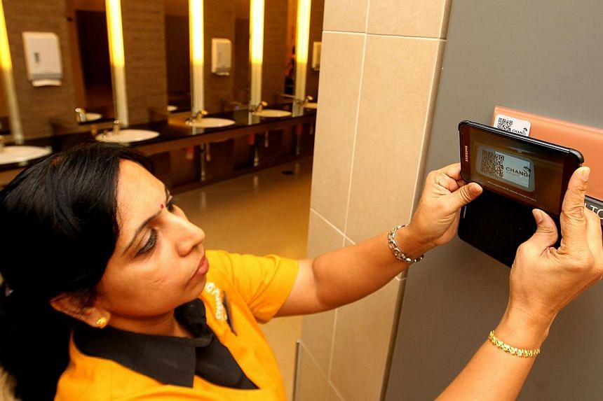 Housekeeping Supervisor Sumathi utilising the E-inspection system. Through Changi Airport's E-inspection system, maintenance staff can report faults to contractors using smartphones installed with specialised software, and keep tabs on repair progres