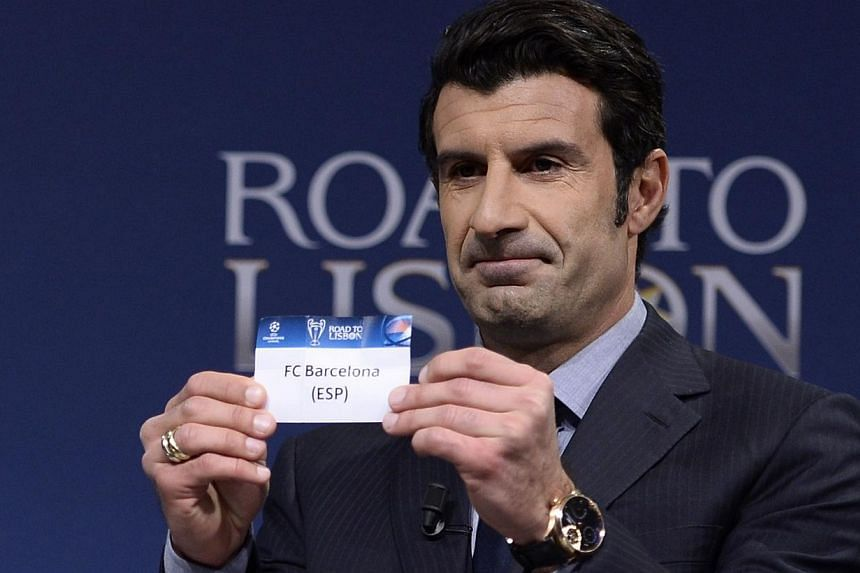 Uefa Champions League Final Ambassador, former Portuguese international footballer Luis Figo holds up the name of Barcelona during the draw for the last 16 of the Uefa Champions league tournament at the UEFA headquarters in Nyon, on Dec 16, 2013. &nb