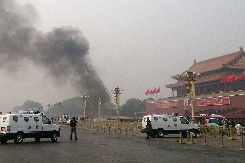 Police cars blocking off the roads leading into Tiananmen Square as smoke rises into the air after a vehicle loaded with petrol crashed in front of Tiananmen Gate in Beijing in an attack which left two people dead, besides the three in the car, and 4
