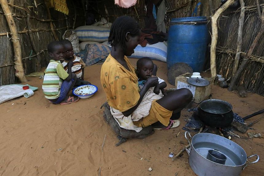 An internally displaced woman feeds her child at the vicinity of an African Union - United Nations Hybrid Operation in Darfur (UNAMID) base near Labado, South Darfur, on Dec 9, 2013. Almost two million people are displaced in Darfur, the United Natio
