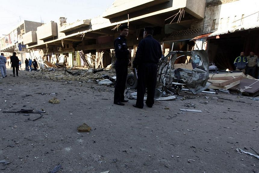 Iraqi policemen inspect the site of car bomb attack in Baghdad, on Dec 16, 2013. A series of bombings in and around the Iraqi capital Baghdad killed at least nine people on Monday, Dec 16, 2013, security and medical officials said.-- PHOTO: REU