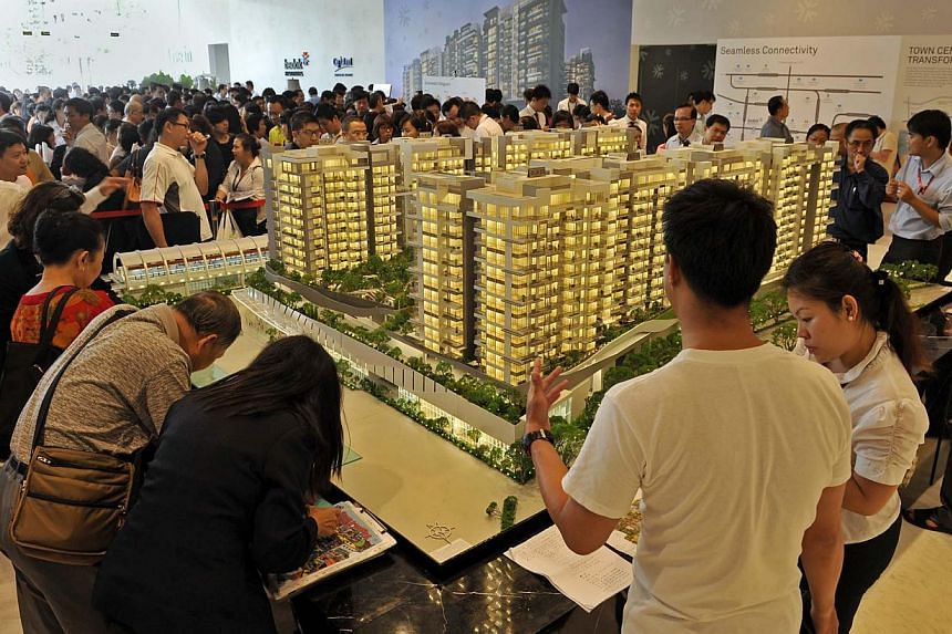 Prospective buyers and property agents checking out the list of units at the condominium showflat. Buying demand took a turn last month as buyers picked up 1,228 new private homes from developers. -- ST FILE PHOTO: RAJENDRAN NADARAJAN