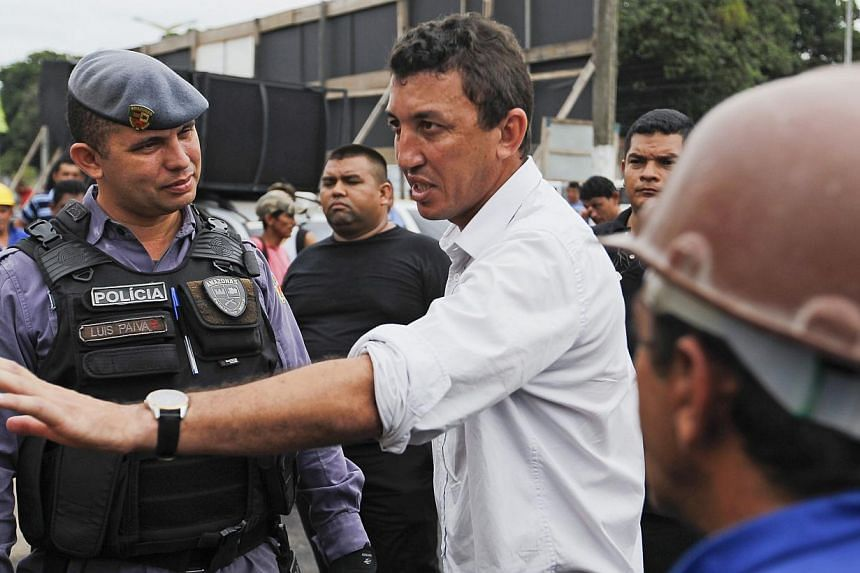 Cicero Custodio (centre), vice president of the Civil Construction Workers' Union talks with employees of the Andrade Gutierrez construction company outside the Arena Amazonia stadium after work was suspended by a labor court following the accidental