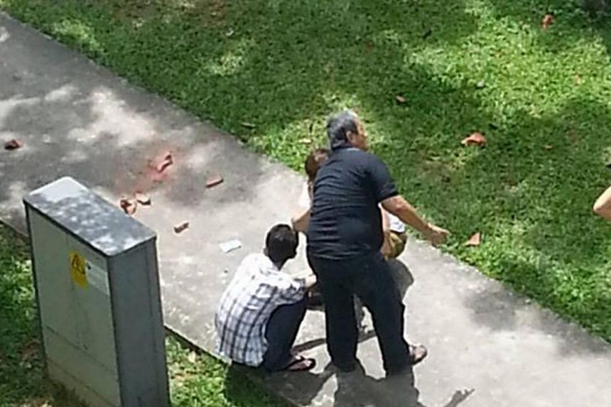 A man is seen injured after being hit by a brick thrown from a flat on Dec 13, 2013. A 15-year-old teenager has been arrested for his suspected involvement in a series of rash acts by throwing items from his flat in eastern Singapore. -- PHOTO: TAN H