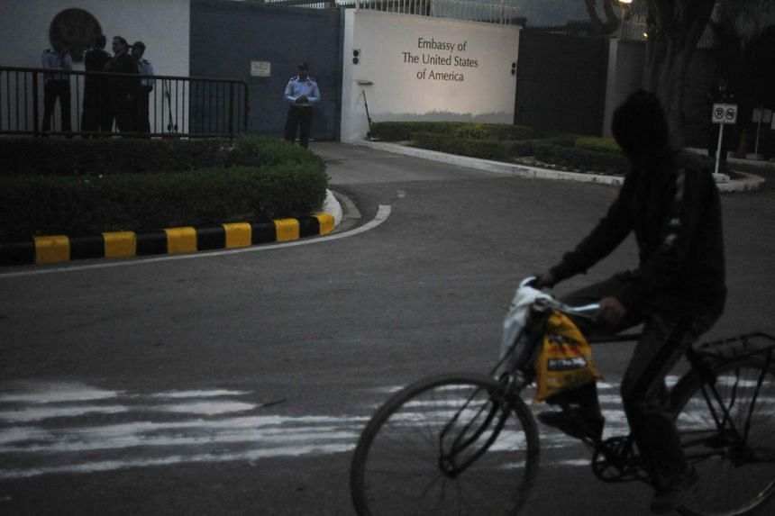 US embassy security personnel watch after barricades were removed in front of the US Embassy in New Delhi on Dec 17, 2013. -- PHOTO: AFP