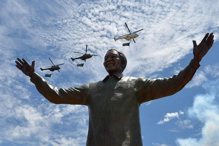 """Helicopters carrying the South African flag fly over a 9-meter bronze statue of South African former president Nelson Mandela which was unveiled on Dec 16, 2013.One of the world's most revered names, """"Mandela"""" has also become a money-spinning b"""