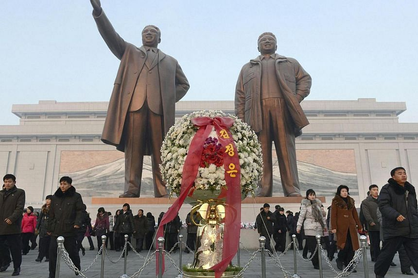 North Koreans offering flowers to bronze statues of North Korea's late founder Kim Il Sung and late leader Kim Jong Il (right) at Mansudae in Pyongyang on Tuesday, Dec 17, 2013, to mark the second death anniversary of Kim Jong Il. North Korean leader