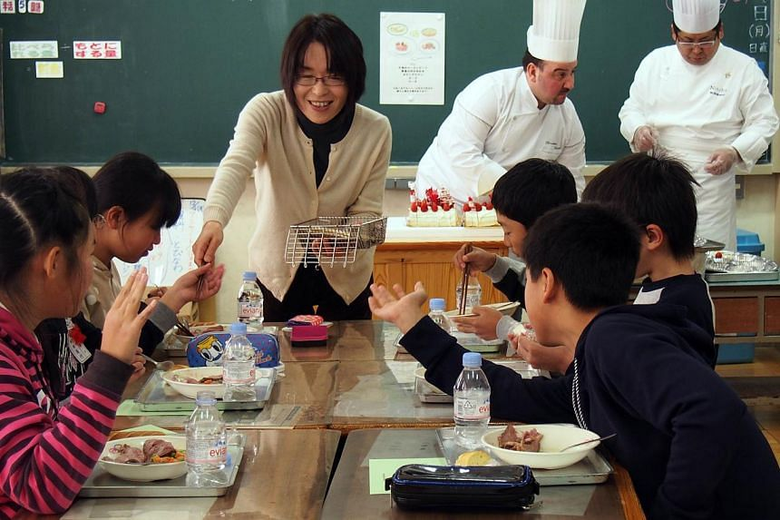 Pupils eating French cuisine and cakes prepared by Caravan Bon Appetite at an elementary school in Koriyama on Dec 9, 2013. -- FILE PHOTO: AFP