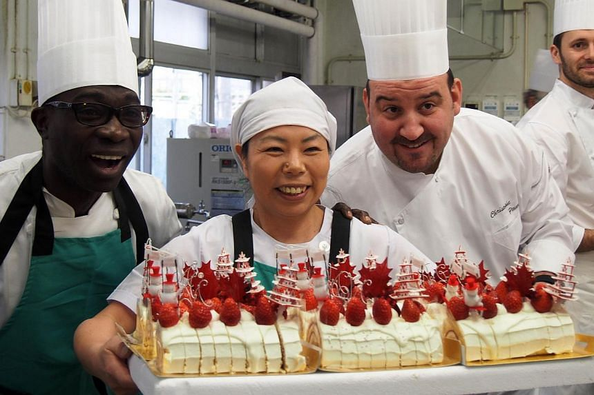 "Chefs from Caravan Bon Appetite with the cake they have prepared at an elementary school in Koriyama on dec 9, 2013. Caravan Bon Appetite"" is an initiative of French chefs in Japan who originally rushed to help provide basic food to survivors of the"