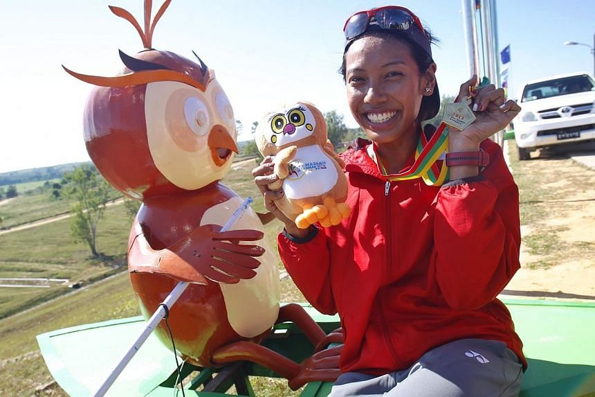 Singapore's Saiyidah Aisyah Mohamed Rafa'ee wins the gold medal in rowing's lightweight single sculls category at Ngalaik dam during the 27th SEA Games in Naypyidaw, Myanmar,on Tuesday, Dec 17 2013. -- ST PHOTO: KEVIN LIM