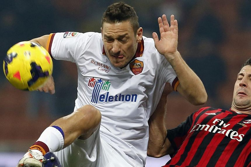 AC Milan's Daniele Bonera (right) challenges AS Roma's Francesco Totti during their Italian Serie A soccer match at San Siro stadium in Milan, on Dec 16, 2013. Totti ended a two-month injury absence for Roma but had to settle for a share of the