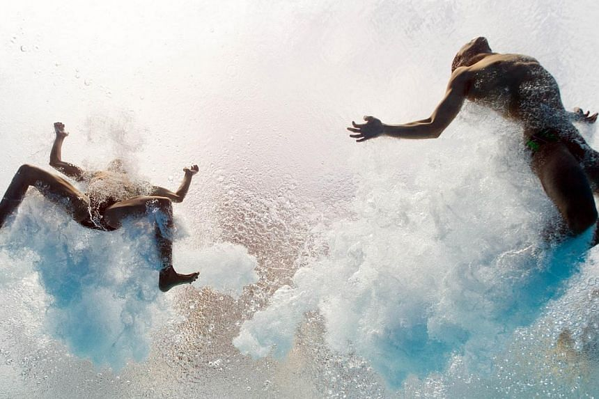 In a picture taken with an underwater camera Mexico's Ivan Garcia and German Sanchez enter the water as they compete in the men's 10-metre synchro platform preliminary diving event in the FINA World Championships at the Piscina Municipal de Montjuic