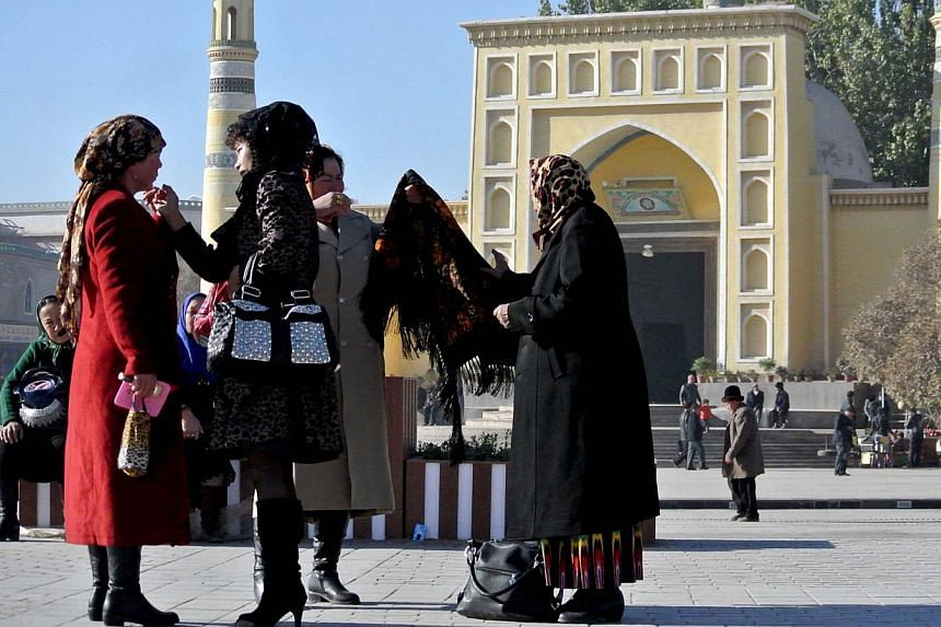 A group of Uighur women outside a mosque in Kashgar, Xinjiang, in November 2013. Two policemen and 14 members of the mostly Muslim Uighur ethnic minority were killed in a clash region near Kashgar on Sunday, Dec 15, 2013. -- FILE PHOTO: AFP