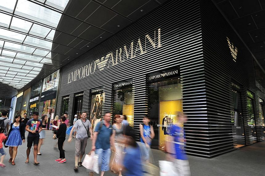 Shoppers walk past the boutique of Emporio Armani at Mandarin Gallery in Orchard Road on July 17, 2013.Singaporeans are preparing to paint the town red this Christmas season, with plans to spend more on gifts this year than last year, according