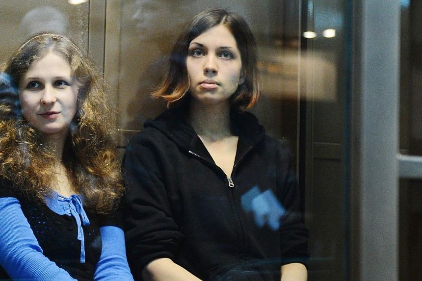 "A file picture taken on Oct 10, 2012, shows two jailed members of the all-girl punk band ""Pussy Riot,"" Maria Alyokhina (left) and Nadezhda Tolokonnikova, sitting in a glass-walled cage in a court in Moscow. Russian lawmakers approved on Wednesd"