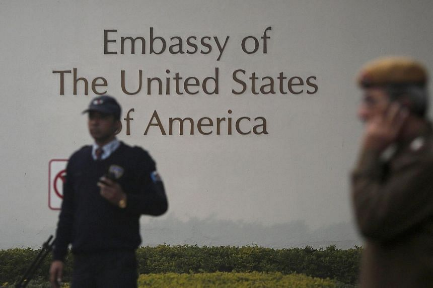 A U.S. embassy security guard (left) and an Indian policeman stand in front of the main gate of the embassy as the bulldozer (unseen) removes the security barriers, in New Delhi Dec 17, 2013. Indian authorities removed security barriers in fron