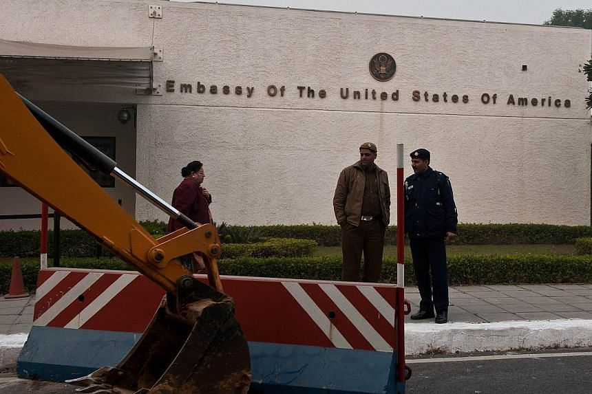 Indian policemen watch as a bulldozer removes a barricade in front of the US Embassy in New Delhi on Dec 17, 2013. Indian authorities removed concrete security barriers in front of the US embassy in New Delhi on Tuesday in apparent retaliation f