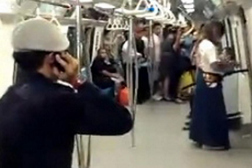 A screenshot from a cellphone video shows a police officer facing off against a man who wields a samurai sword on board an MRT train on Dec 16, 2013. Police have confirmed that the man arrested for wielding the sword in public is called Peter Chua. -