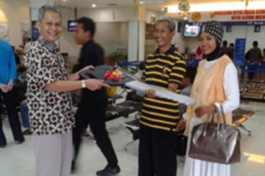 Mr and Mrs Zaenal Muttaqin receiving a symbolic key to a Yamaha motorcycle prize that they won from saving money at Jakarta-based Bank Central Asia. -- PHOTO: BANK CENTRAL ASIA