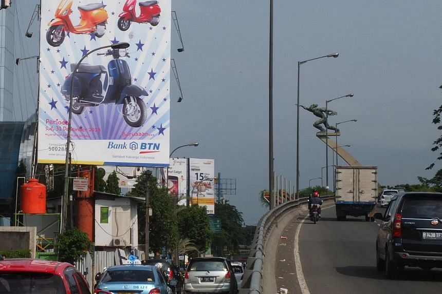 A Bank Tabungan billboard on a main Jakarta street shows off its prizes to attract depositors. It gives away a Vespa motorcycle for depositors who are willing to put 60 million rupiah (S$6,200) savings and not withdraw it for several years. -- PHOTO: