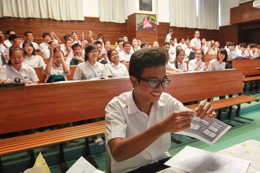 Classmates cheer as Temasek Secondary School's Abdul Haziq B Abdul Hafis S (foreground) collects his N-level examinations results on Thursday, Dec 19, 2013. -- ST PHOTO: NEO XIAOBIN