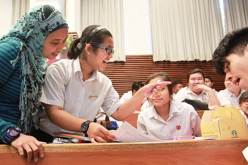 Temasek Secondary School's Siti Halimatussa'adiah Bte Saidi (second from left) reacts as her classmates and Allied Educator (AED) for Learning & Behavioural Support Madam Nur Khairunnisa (left) check out her N-level examinations results at the au