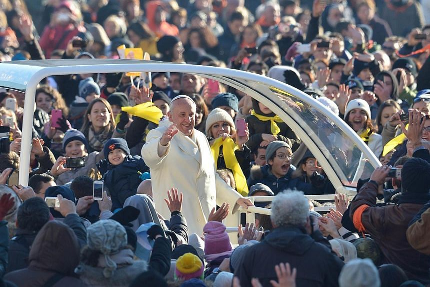 Pope Francis (centre) greets the crowd as he arrives for his general audience at St Peter's square on Dec 18, 2013 at the Vatican. More than two million people have flocked to Pope Francis' general audiences in St. Peter's Square since his election i