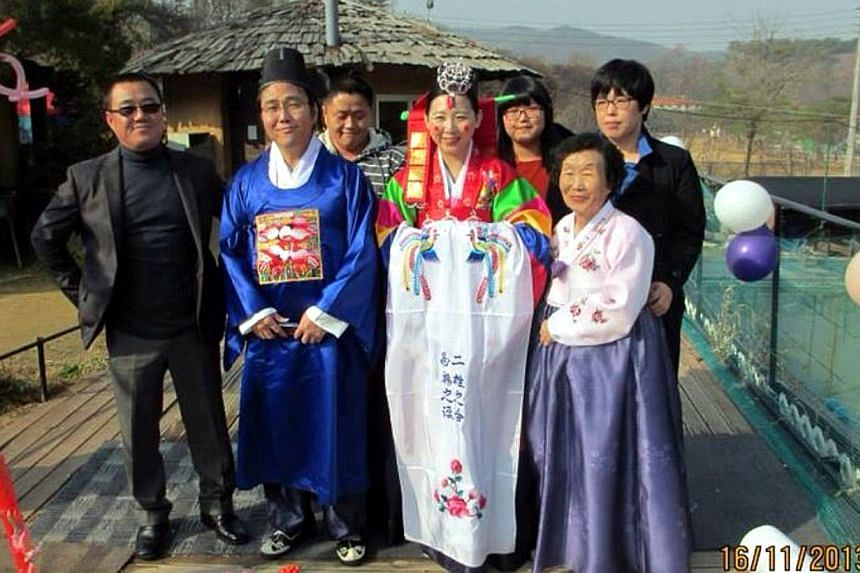 Yen, a programme producer from Singapore, going through traditional Korean wedding rites with her husband Dae Sik in Gimpo, South Korea. She is surrounded by her mother-in-law (on her left) and the rest of her husband's family. -- PHOTO: YEN