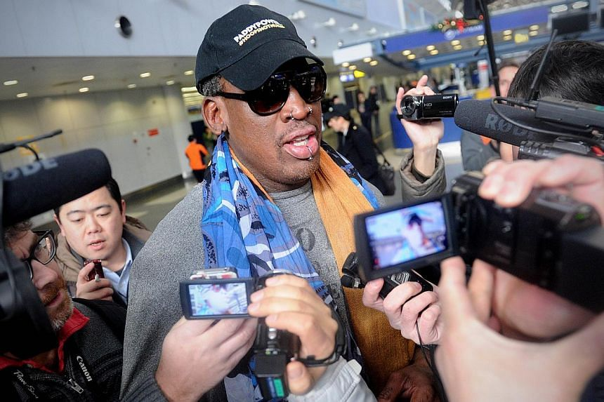Former US NBA basketball player Dennis Rodman (centre) speaks to members of the media as he makes his way through Beijing's international airport on Dec 19, 2013. Rodman said on Thursday he was not going to North Korea to talk about politics or human