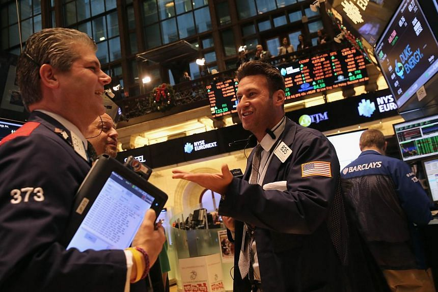 Traders work the floor of the New York Stock Exchange after the Dow Jones Industrial Average closed up 293 points on Dec 18, 2013 in New York City. US stocks on Wednesday surged to new records after the US Federal Reserve modestly scaled back its bon