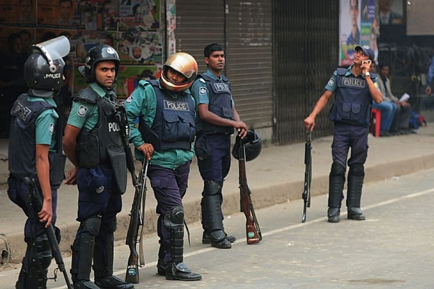 Bangladeshi police stand guard during a blockade organised by Bangladesh Nationalist Party (BNP) activists and their supporters in Dhaka on Dec 19, 2013. Bangladesh's main opposition party has called for a 72-hour blockade, rejecting plans for a Jan
