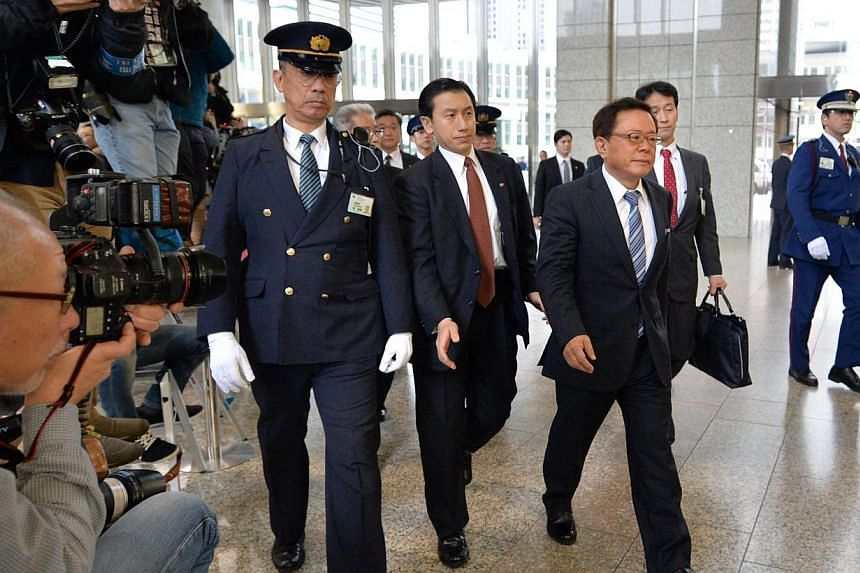 Tokyo governor Naoki Inose (front, right) arrives at the Metropolitan Government Building in Tokyo on Dec 19, 2013. The governor of Tokyo has submitted his resignation after admitting receiving US$500,000 (S$630,000) from a hospital tycoon ahead of h