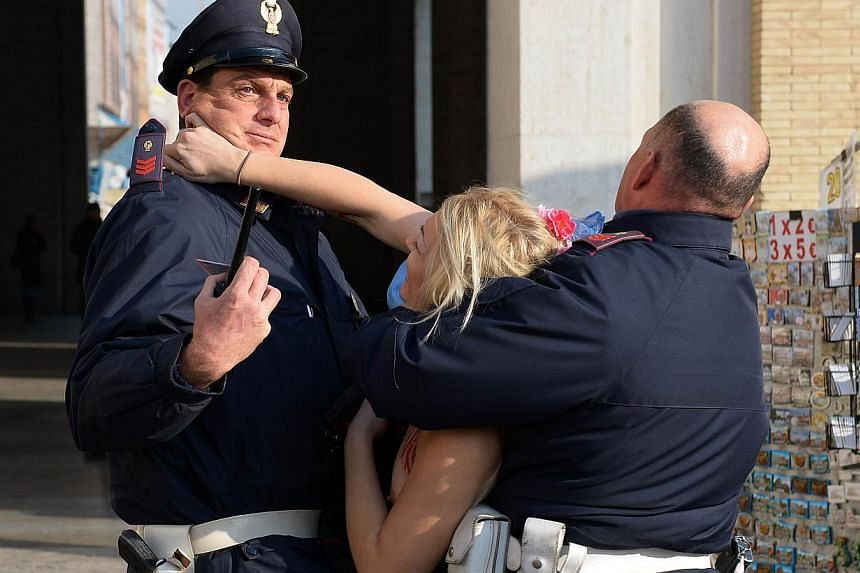 Inna Shevchenko, leader of the Ukrainian feminist protest group Femen is held by policemen outside Saint Peter's Square in the Vatican, on Dec 19, 2013. A leader of the Ukrainian feminist group Femen bared herself near St Peter's Square on Thursday,