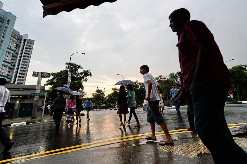 People walk on the street in the Little India on Dec 15, 2013. The number of private buses ferrying workers to Little India will be halved this Sunday, and they will stop operating two hours earlier. -- FILE PHOTO: AFP