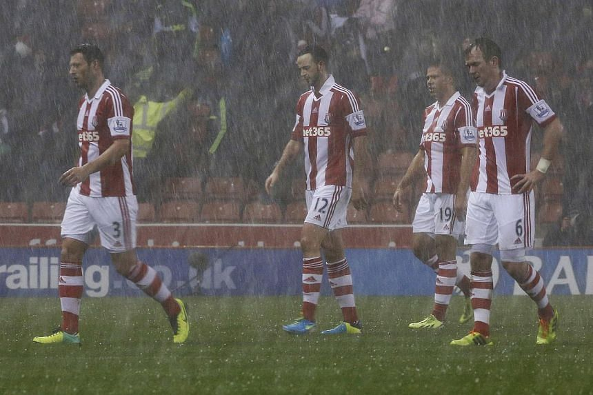 Stoke City players walk off after referee Mark Clattenburg (not pictured) suspended play temporarily due to bad weather during their English League Cup quarter-final soccer match against Manchester United at the Britannia stadium in Stoke-on-Trent, c
